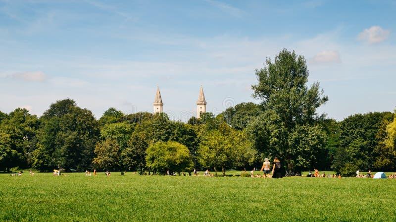 Horizonte de Munich de Englischer Garten, Alemania Los Locals y los turistas disfrutan de un día de verano caliente en el parque foto de archivo libre de regalías