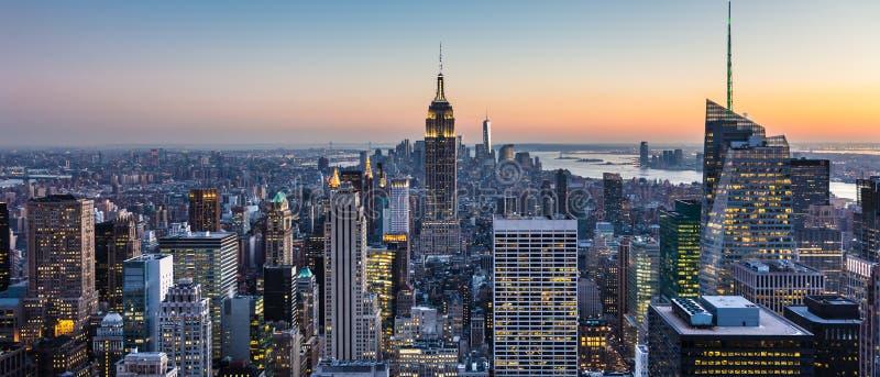 Horizonte de New York City con los rascacielos urbanos en la oscuridad, los E fotos de archivo libres de regalías