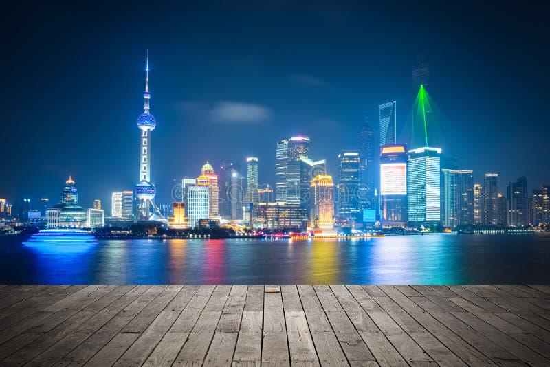 Horizonte de Shangai en la noche con el piso de madera foto de archivo
