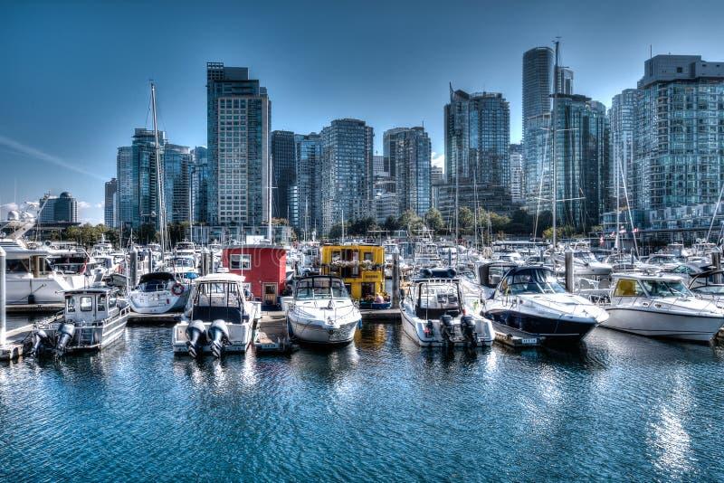 Horizonte de Vancouver con los barcos y las casas barco en el puerto deportivo foto de archivo