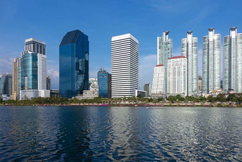 Horizonte del capital de Bangkok del distrito financiero durante el cielo azul del tiempo del día con la opinión del lago fotos de archivo