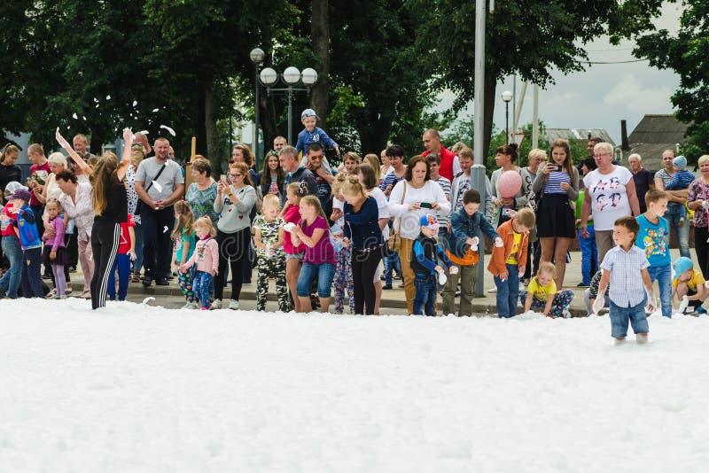 HORKI, БЕЛАРУСЬ - 25-ОЕ ИЮЛЯ 2018: Дети различных возрастов играют с белой пеной в парке на партии после обеда стоковое изображение