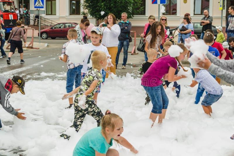 HORKI, БЕЛАРУСЬ - 25-ОЕ ИЮЛЯ 2018: Дети различных возрастов играют с белой пеной в парке на партии в летнем дне стоковые фото