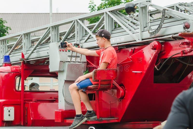 HORKI, БЕЛАРУСЬ - 25-ОЕ ИЮЛЯ 2018: Мальчик принимает selfie на красной спасательной службе 112 автомобиля на празднике в парке на стоковое фото rf