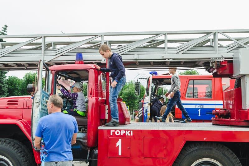 HORKI, BIELORRÚSSIA - 25 DE JULHO DE 2018: As crianças de idades diferentes jogam nos carros vermelhos do serviço de salvamento 1 foto de stock