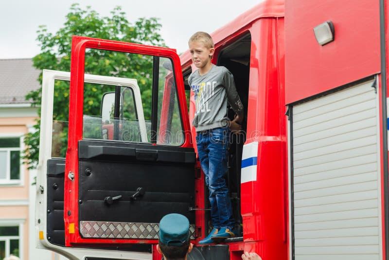 HORKI VITRYSSLAND - JULI 25, 2018: Pojken ser ut ur den röda räddningstjänsten 112 som bilen på en ferie i parkerar på en sommard royaltyfria foton