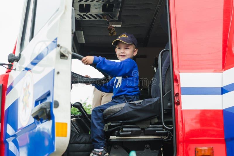 HORKI VITRYSSLAND - JULI 25, 2018: Pojken sitter bak styrningen rullar en röd bilräddningstjänst 112 på en ferie i parkerar in royaltyfria foton