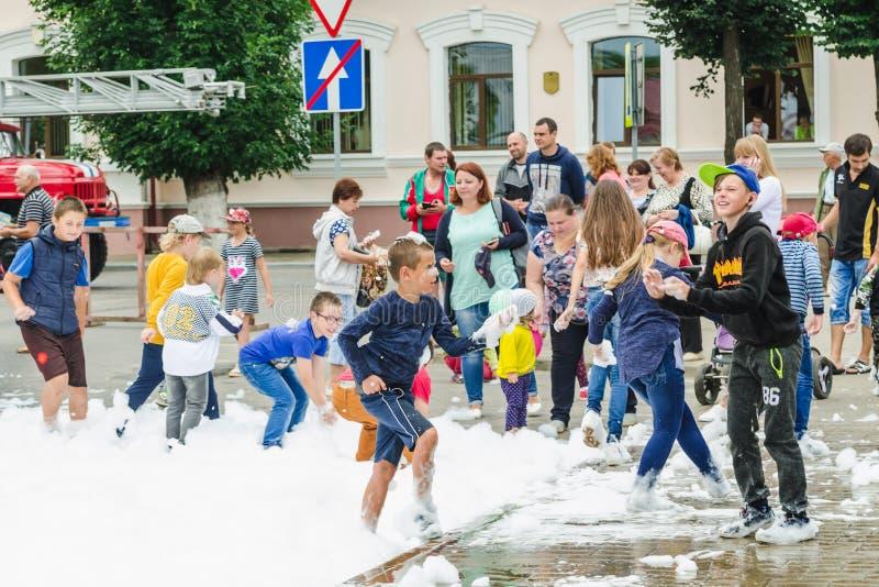 HORKI, WEISSRUSSLAND - 25. JULI 2018: Kinder des unterschiedlichen Alters spielen mit weißem Schaum im Park an einer Partei am So lizenzfreies stockfoto