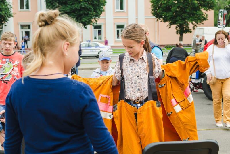 HORKI, WIT-RUSLAND - JULI 25, 2018: Weinig blondemeisje kleedt een oranje kostuum van de redderdienst 112 op een de zomerdag in e stock afbeeldingen