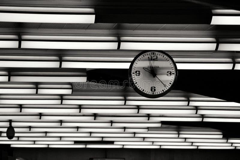 Horloge accrochant sur le fond clair photographie stock