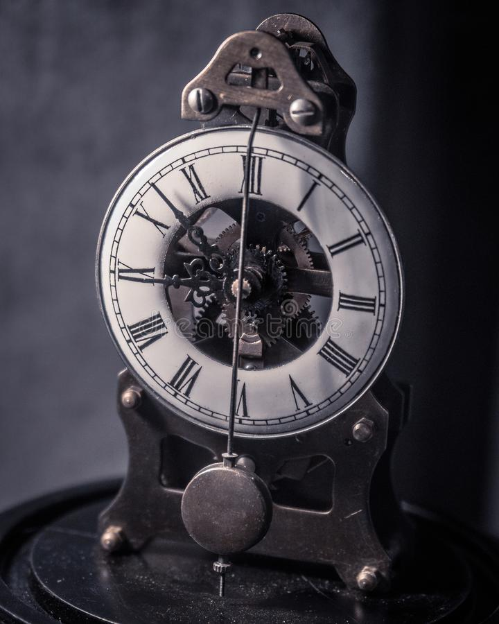 Horloge antique de vintage avec le pendule et les couleurs amorties image libre de droits