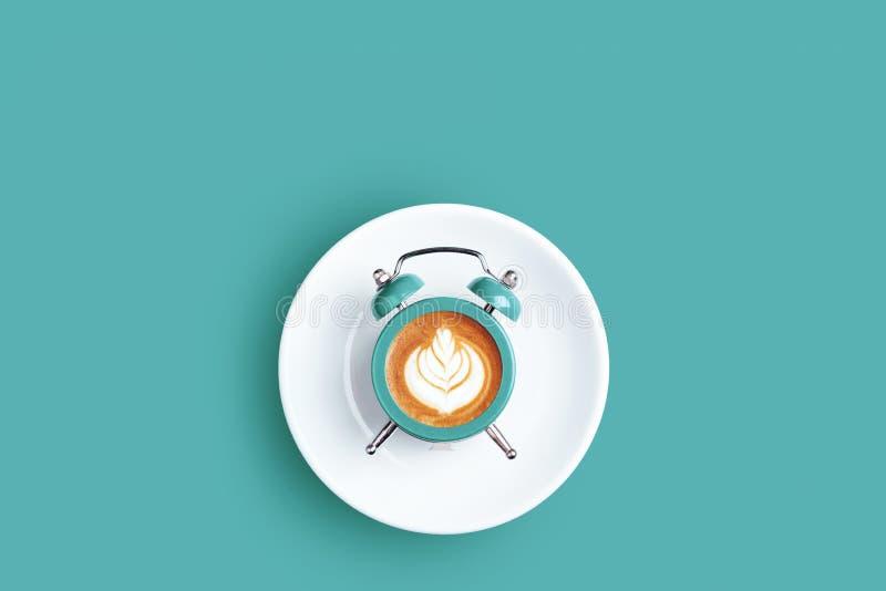 Horloge avec le cadran du café sur le fond de turquoise image stock