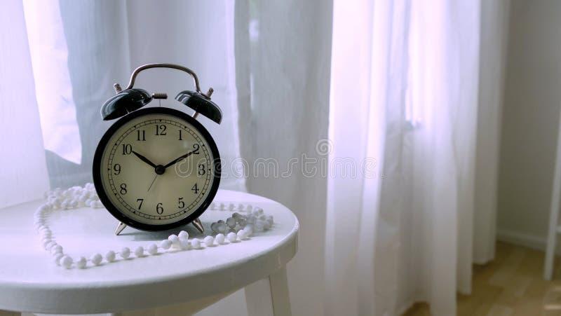Horloge classique sur la table blanche dans la chambre à coucher photo libre de droits