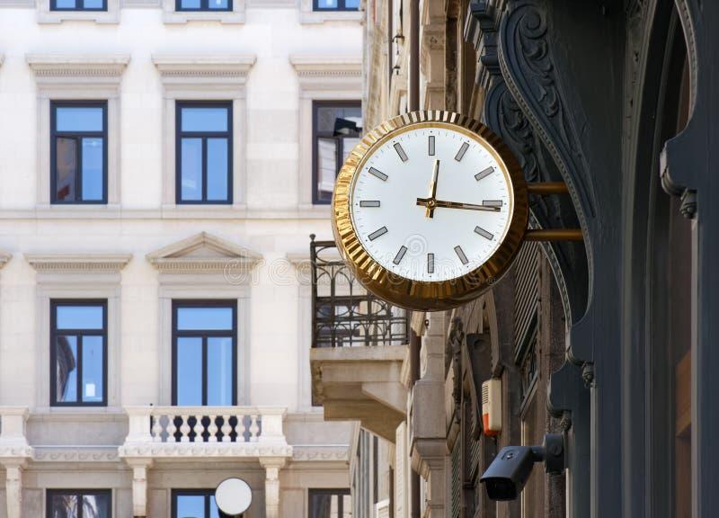 Horloge colorée d'or dans un contexte urbain photos stock