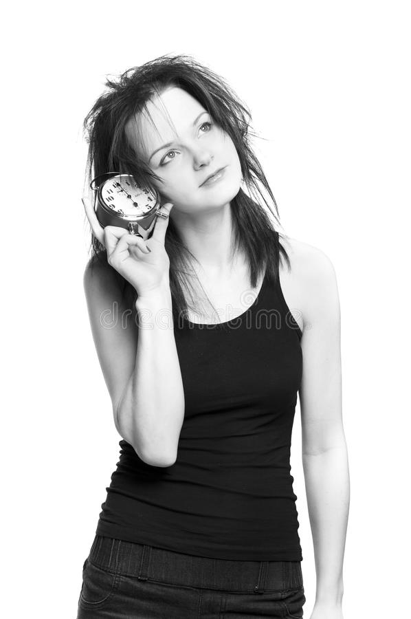 Horloge d'alarme épuisée de fixation de fille photographie stock