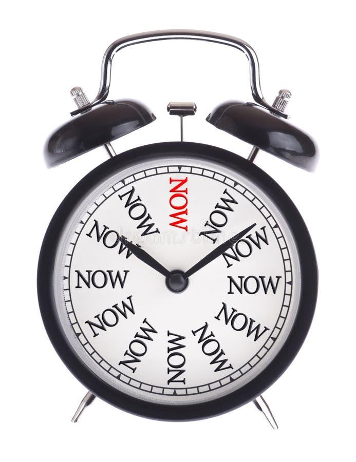 Horloge d'alarme avec le mot maintenant photographie stock libre de droits