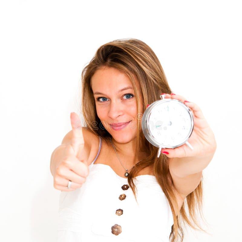 Horloge d'alarme de fixation de femme avec des pouces vers le haut photo libre de droits