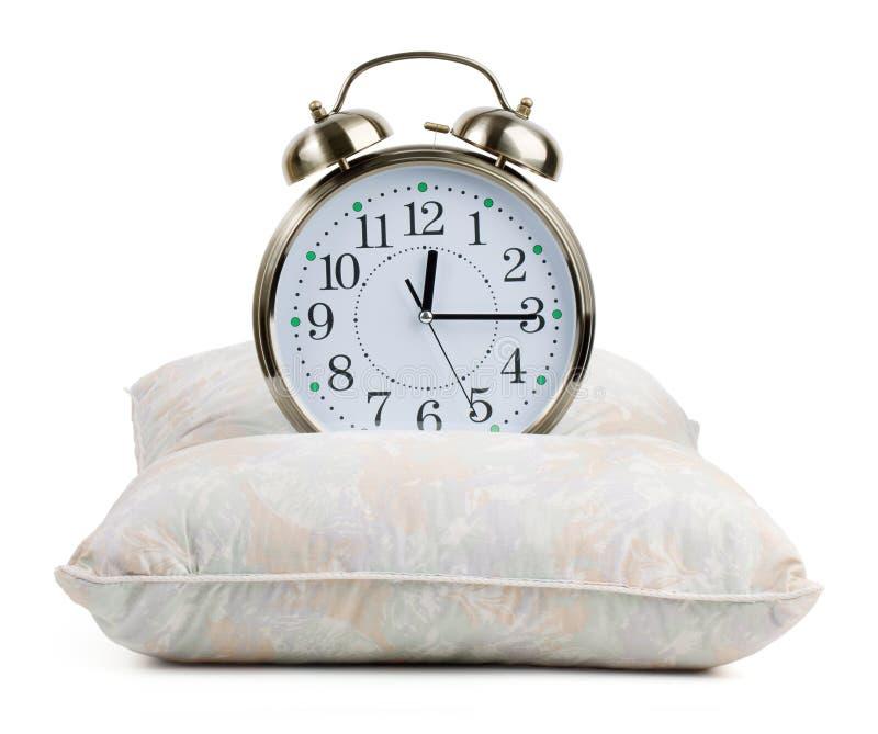 Horloge d'alarme en métal sur un oreiller images libres de droits