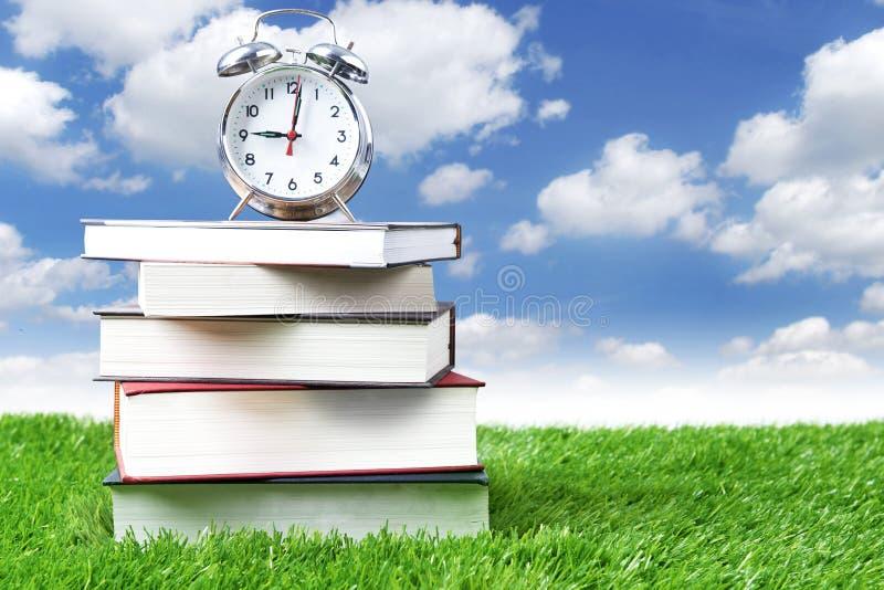 Horloge d'alarme et pile de livres photographie stock