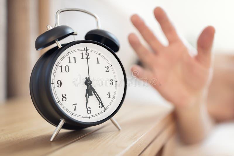 Horloge d'alarme heure de réveil matinale sur la table de chevet avec l'homme qui tend à arrêter la cloche images libres de droits