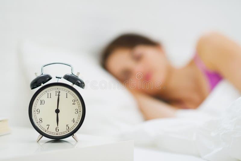 Horloge d'alarme sur la table et la femme à l'arrière-plan photos libres de droits