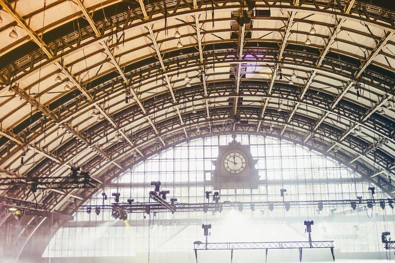 Horloge de cru devant le vieil intérieur industriel avec les voûtes et les plafonniers en acier Contre-jour blanc au moment de l' image stock