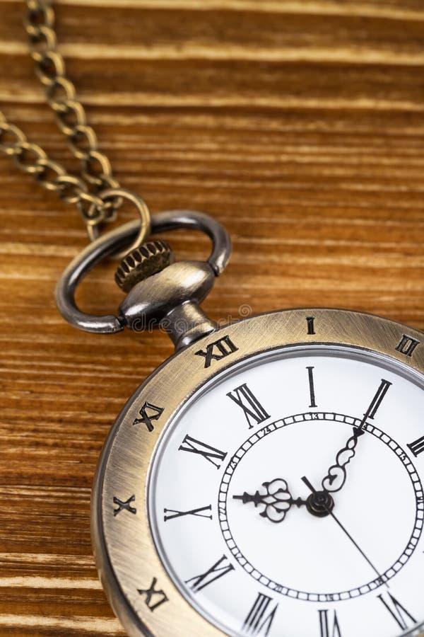 Horloge de montre de poche de cru sur le fond en bois photos stock