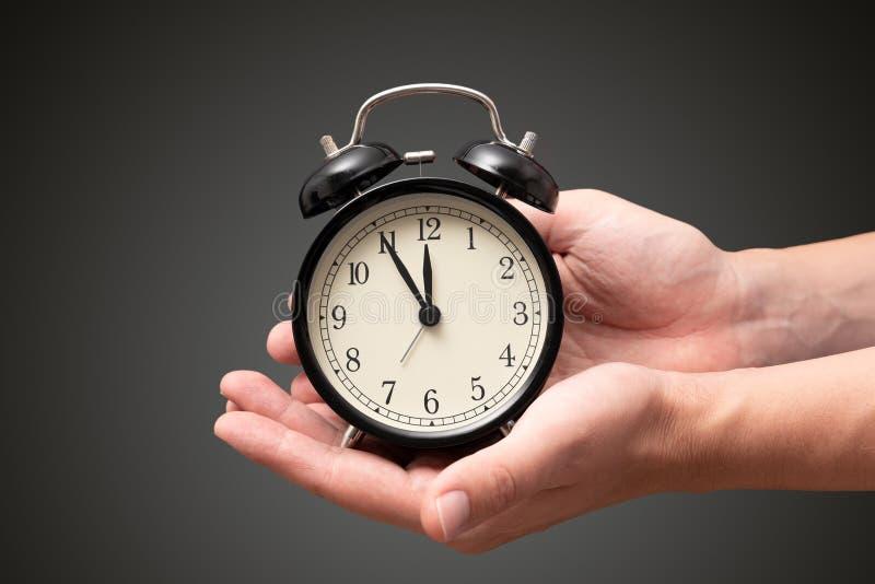 Horloge de participation de main avec cinq minutes à douze heures photos libres de droits