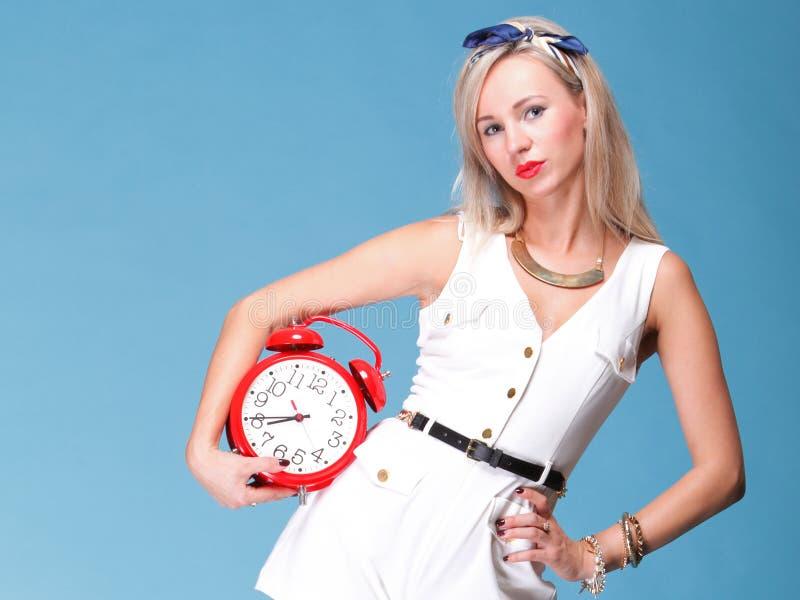 Horloge de rouge de femme assez jeune de verticale photos stock