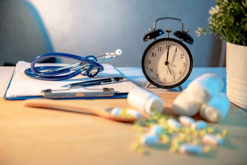 Horloge de stéthoscope, de presse-papiers et de table sur le bureau de docteur images stock