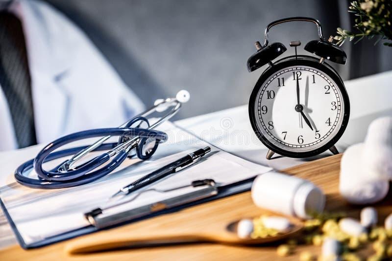 Horloge de stéthoscope, de presse-papiers et de table sur le bureau de docteur photos libres de droits