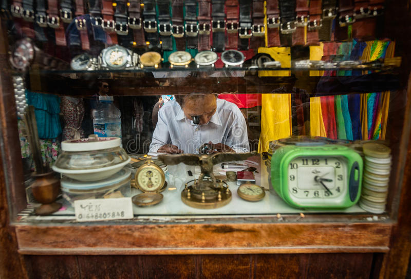 Horloge en klok de reparatiemens beoefent zijn handel bij een straattribune royalty-vrije stock afbeeldingen