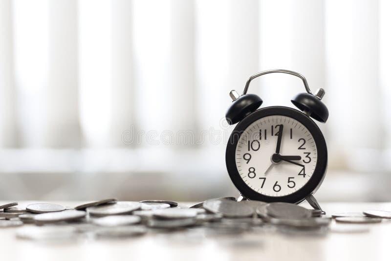 Horloge et pièces de monnaie sur la fenêtre de secteur de table de bureau, le temps, c'est de l'argent image stock