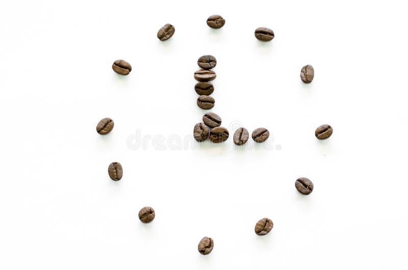 Horloge faite à partir des grains de café sur le fond blanc, café d'amour photos stock
