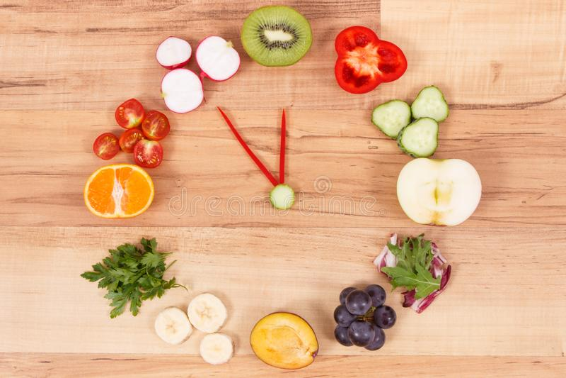 Horloge faite de fruits et légumes contenant les minerais, heure pour des résolutions de concept sain de nutrition photos stock