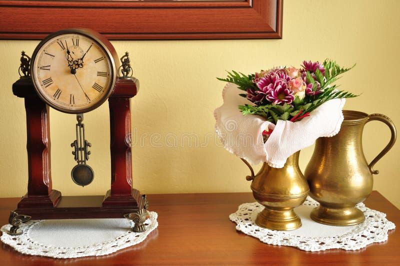 Horloge, fleurs et vases photos stock