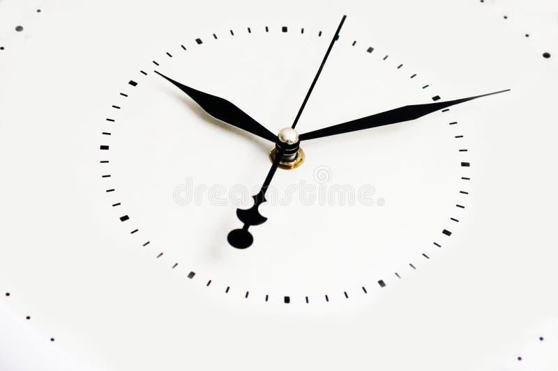 Horloge murale blanche avec les flèches noires images stock