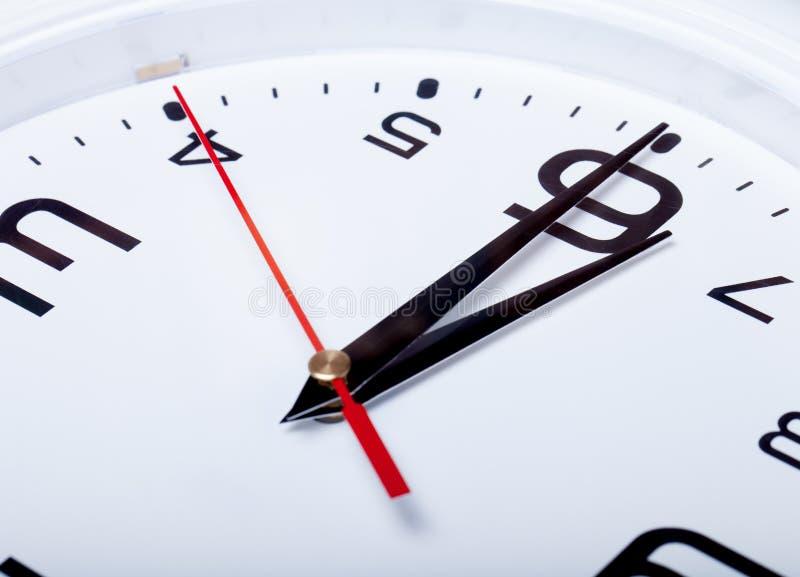 Horloge murale blanche avec les flèches noires Foyer sélectif Département peu profond photographie stock libre de droits