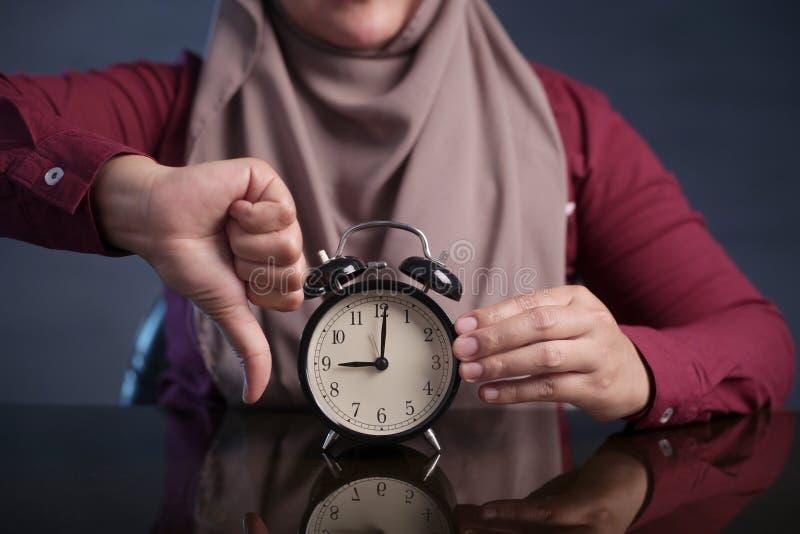 Horloge musulmane de participation de femme se dirigeant à neuf O& x27 ; Horloge, concept de retard photo libre de droits