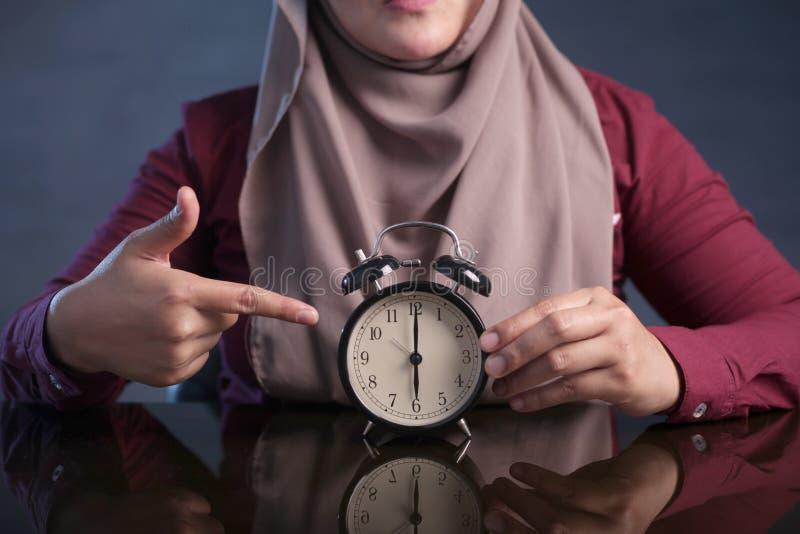 Horloge musulmane de participation de femme se dirigeant chez six O& x27 ; Horloge images stock