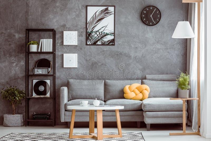 Horloge noire au-dessus de canapé gris images libres de droits
