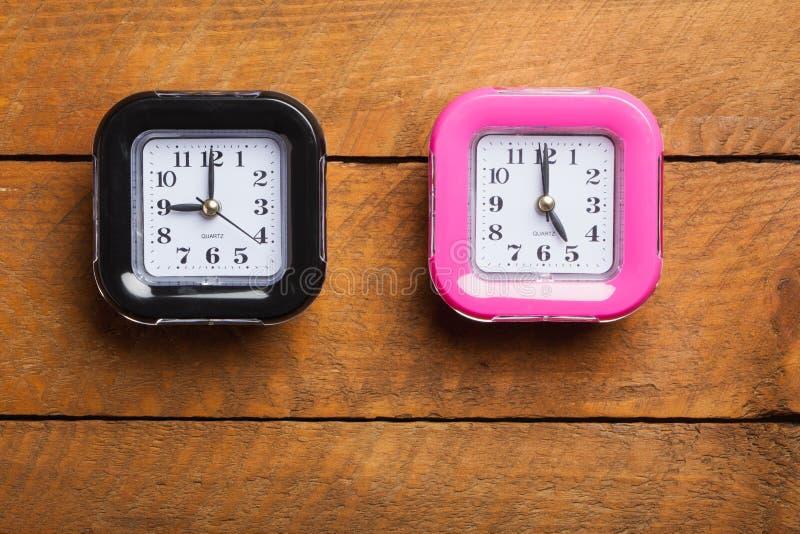 Horloge noire et rose, neuf à cinq, heures de bureau image libre de droits