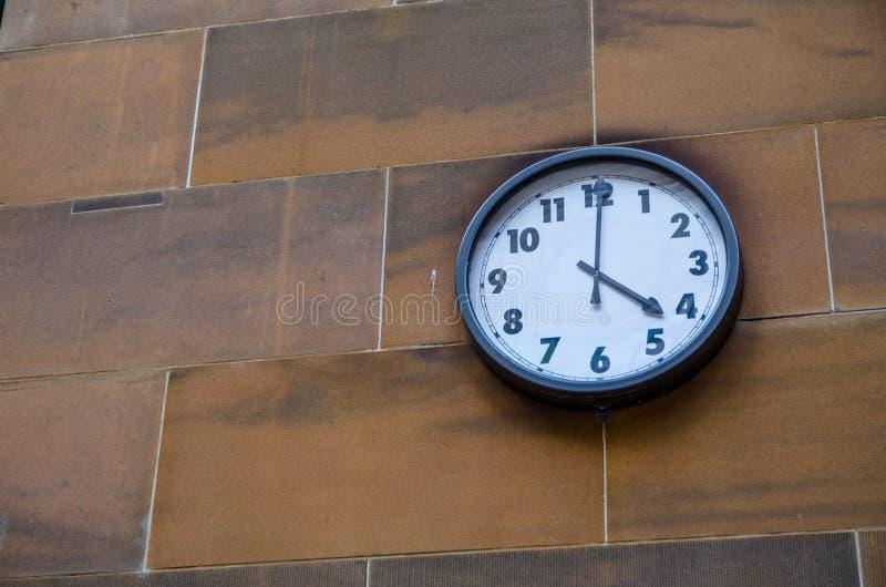 Horloge ronde avec le chiffre arabe attachée sur le mur de briques rouge de sable photographie stock