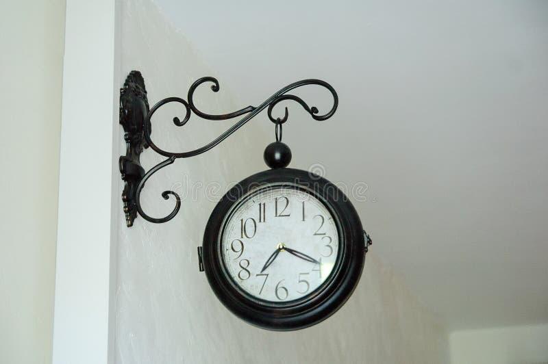 Horloge ronde de vintage en métal sur le mur blanc Le 7h20 d'exposition de flèches photo libre de droits