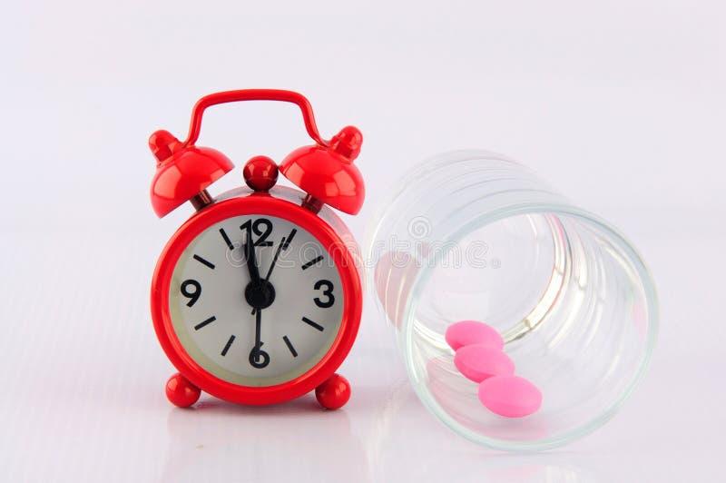 Horloge rouge et tablette rose en glace de dosage sur le fond blanc photos stock