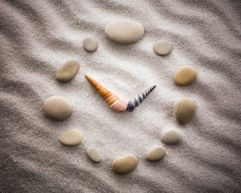 Horloge stylisée de cadran pour des coquilles sur le sable pour la concentration et la relaxation pour l'harmonie et l'équilibre  photos stock