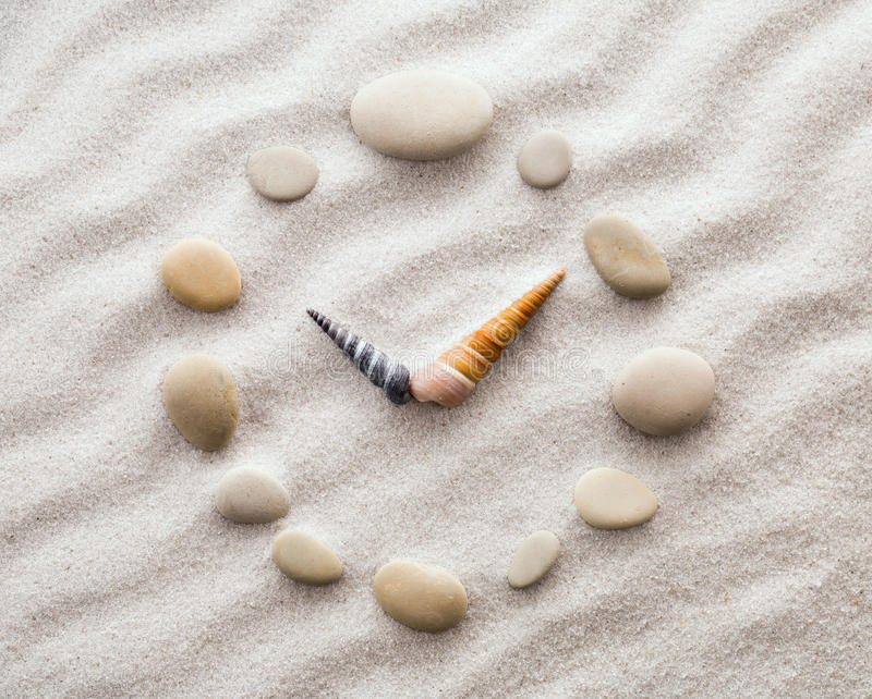 Horloge stylisée de cadran pour des coquilles sur le sable pour la concentration et la relaxation pour l'harmonie et l'équilibre  images stock