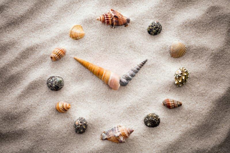 Horloge stylisée de cadran pour des coquilles sur le sable pour la concentration et la relaxation pour l'harmonie et l'équilibre  photographie stock