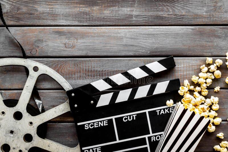 Horlogefilm in bioskoop met popcorn, videoband en clapperboard op houten hoogste mening als achtergrond royalty-vrije stock afbeeldingen