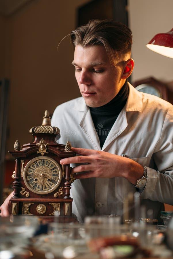 Horloger avec la vieille horloge mécanique de bureau photo stock